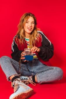 Porträt des jungen blonden mädchens in den retro-stilkleidung der 90er jahre
