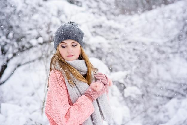 Porträt des jungen blonden mädchens während des schneefalls