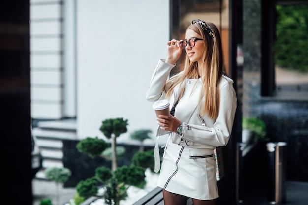 Porträt des jungen blonden modells, das in die stadt geht, mädchen im stilvollen outfit.