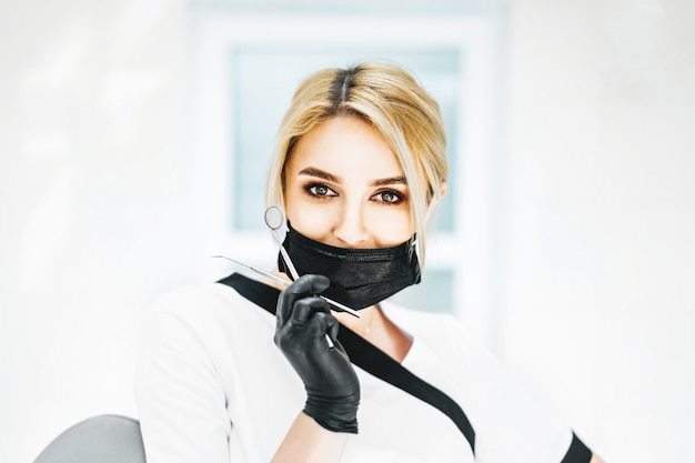 Porträt des jungen blonden weiblichen zahnarztes, der zahnärztliche instrumente hält. eine frau mit schwarzer maske und handschuhen. platz für text