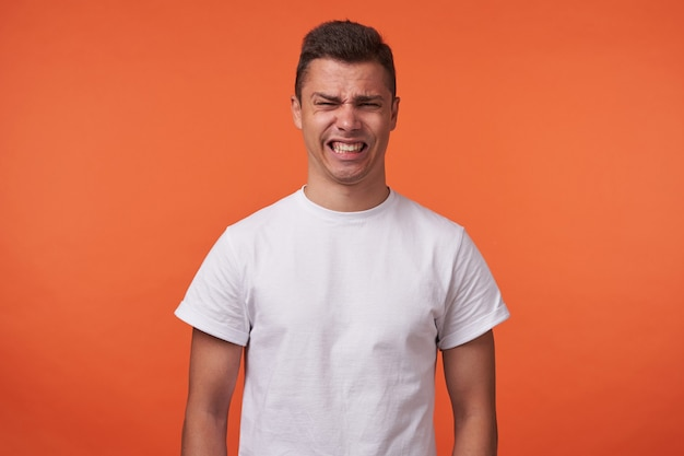 Porträt des jungen brünetten mannes mit kurzem haarschnitt, der sein gesicht verzieht und zähne zeigt, während er kamera betrachtet, über orange hintergrund mit den händen nach unten stehend