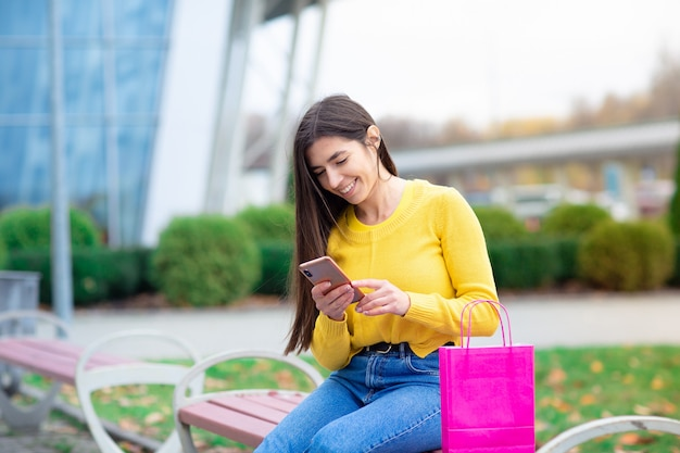 Porträt des jungen brunettefrauensitzens im freien auf bank mit einkaufstaschen und anwendung des handys.
