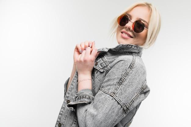 Porträt des jungen charmanten freudigen blonden mädchens in der jeansjacke, die in der runden sonnenbrille auf hintergrund besitzt und gestikuliert