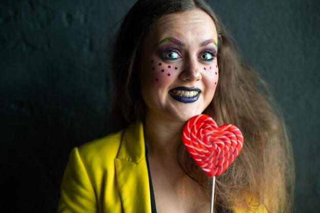 Porträt des jungen clownmädchens, das mit süß aufwirft