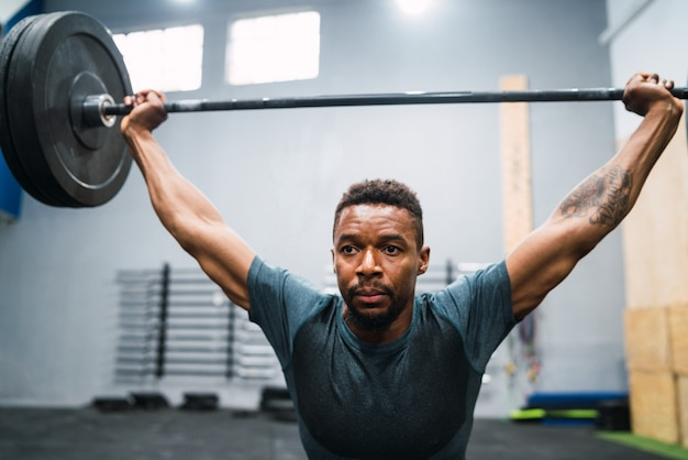 Porträt des jungen crossfit-athleten, der übung mit einer langhantel macht. crossfit, sport und gesundes lifestyle-konzept.