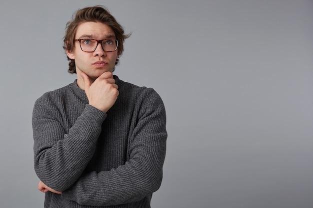 Porträt des jungen denkenden mannes mit brille trägt im grauen pullover, steht über grauem hintergrund mit kopierraum auf der rechten seite, berührt kinn und schaut weg.