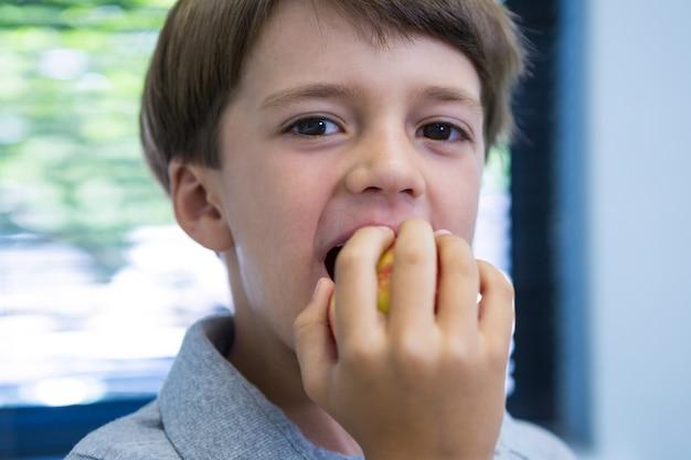 Porträt des jungen, der apfel isst