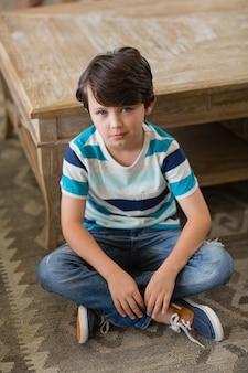 Porträt des jungen, der im wohnzimmer sitzt