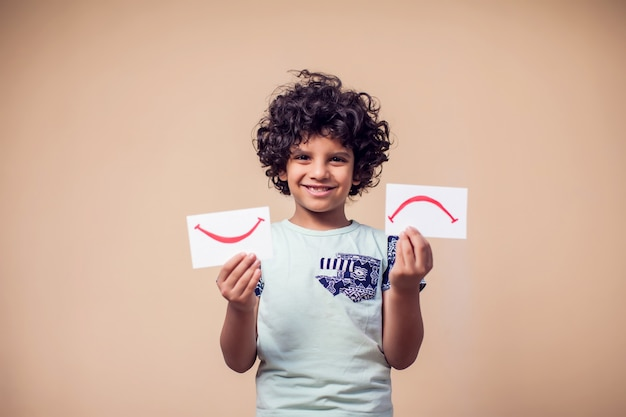 Porträt des jungen, der karten mit positivem und negativem symbol hält. kinder- und emotionskonzept