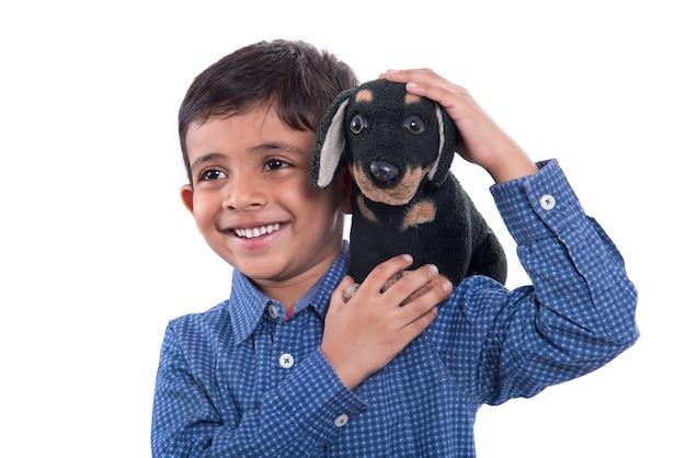 Porträt des jungen, der mit seinem stofftier haustier auf weiß spielt