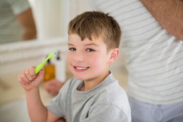 Porträt des jungen, der zähne im badezimmer putzt