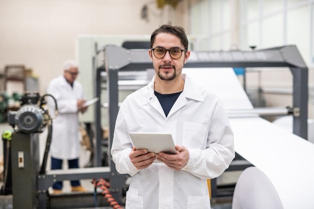 Porträt des jungen druckereiingenieurs im weißen kittel und in den gläsern, die digitale tablette im fabrikladen halten