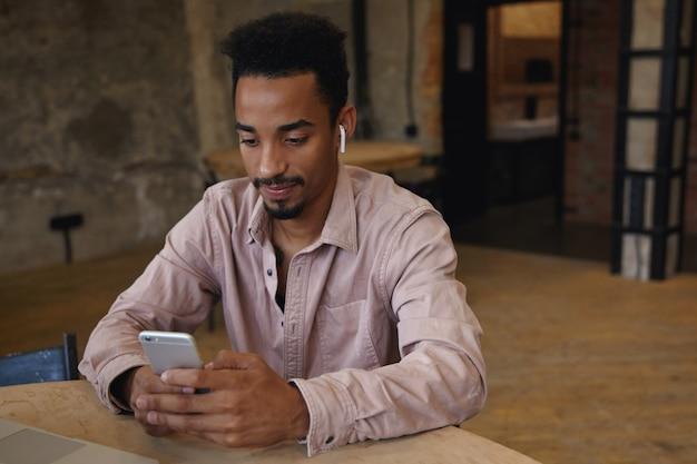 Porträt des jungen dunkelhäutigen mannes mit bart, der auf treffen im coworking space wartet, smartphone in händen hält und bildschirm positiv betrachtet, beige hemd und kopfhörer tragend