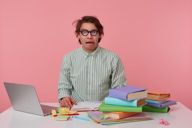 Porträt des jungen dunklen mannes mit wildem dunklem haar, das am arbeitstisch sitzt und notizen macht, grimassen im gestreiften hemd und in den gläsern
