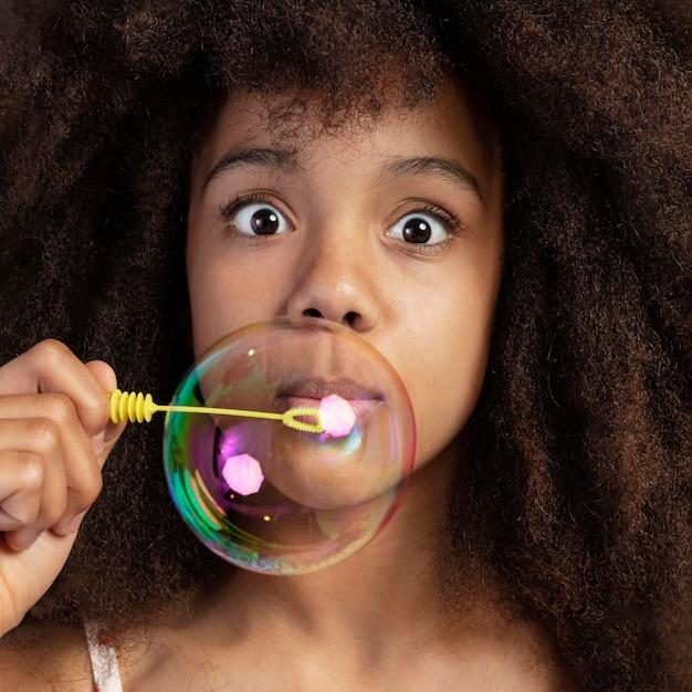 Porträt des jungen entzückenden mädchens, das beim spielen mit seifenblasen aufwirft
