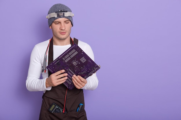Porträt des jungen erfahrenen radiotricians, der isoliert über flieder im studio steht und elektronische leiterplatte hält