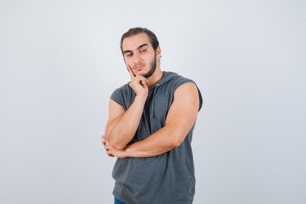Porträt des jungen fitten mannes, der finger auf wange im ärmellosen kapuzenpulli hält und nachdenkliche vorderansicht schaut