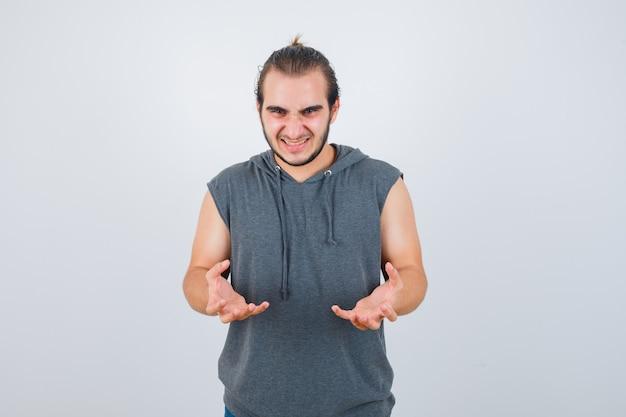 Porträt des jungen fitten mannes, der hände in der aggressiven weise im ärmellosen kapuzenpulli hält und böse vorderansicht schaut