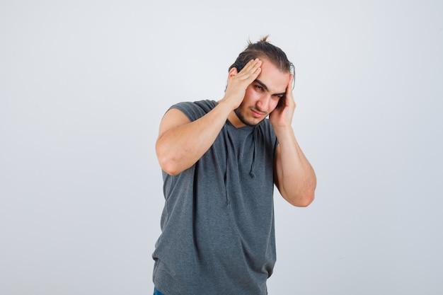 Porträt des jungen fitten mannes, der unter kopfschmerzen im ärmellosen kapuzenpulli leidet und schmerzhafte vorderansicht schaut