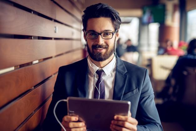 Porträt des jungen freudigen gutaussehenden bärtigen geschäftsmannes im anzug, der musik von einem tablett in einem modernen café hört und in die kamera schaut.