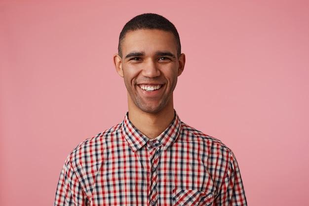 Porträt des jungen fröhlichen attraktiven dunkelhäutigen kerls im karierten hemd, schaut in die kamera mit glücklichem ausdruck, breit lächelnd und steht über rosa hintergrund, positives emotionskonzept.