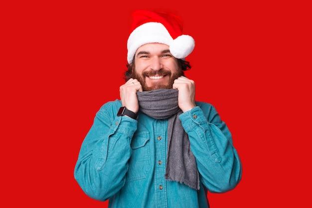 Porträt des jungen fröhlichen bärtigen mannes mit weihnachtsmann-hut auf rotem hintergrund