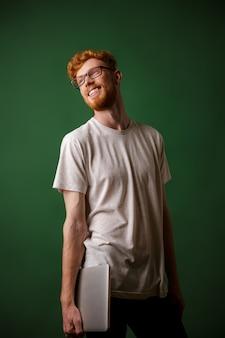 Porträt des jungen fröhlichen bärtigen readhead-hipsters, der laptop hält und wegschaut