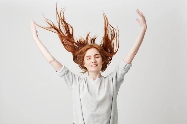 Porträt des jungen fröhlichen schönen rothaarigen mädchens, das mit geschlossenen augen lächelt, die haare schütteln.