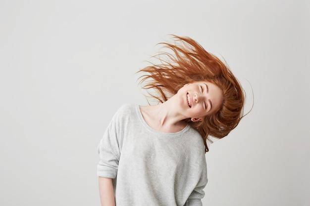 Porträt des jungen fröhlichen schönen rothaarigen mädchens, das mit geschlossenen augen lächelt, die kopf und haare schütteln.
