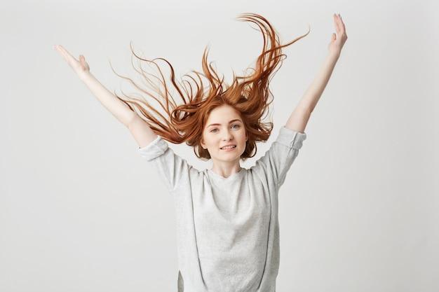 Porträt des jungen fröhlichen schönen rothaarigen mädchens lächelnd schüttelndes haar.