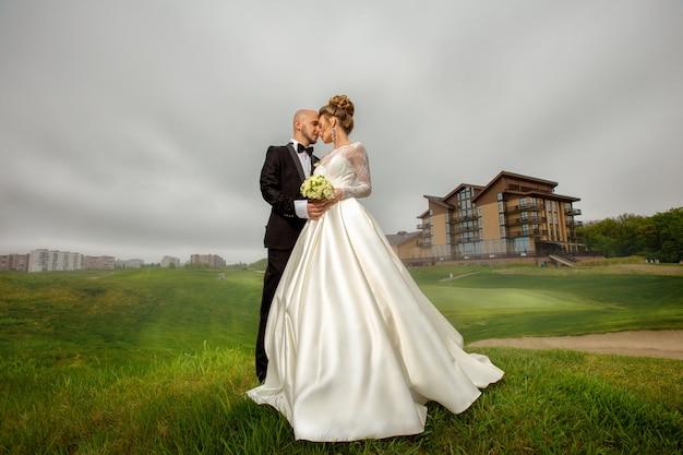 Porträt des jungen gerade verheirateten paares der herrlichen eleganz, das draußen aufwirft