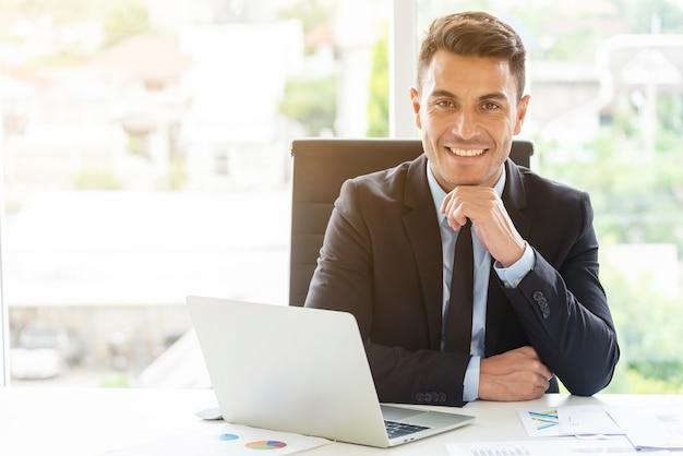 Porträt des jungen geschäftsmannes arbeitend im büro mit lächeln. manager oder intelligentes arbeitendes volk