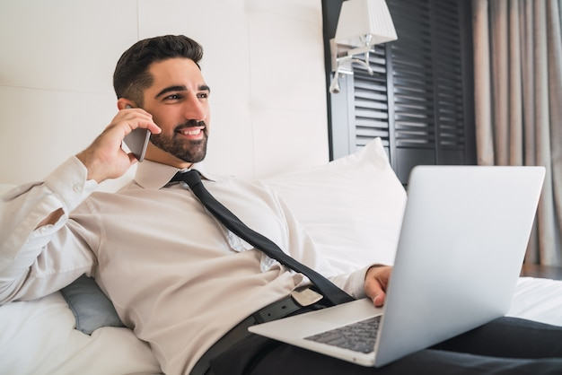 Porträt des jungen geschäftsmannes, der auf bett liegt und am telefon spricht, während er an seinem laptop im hotelzimmer arbeitet. geschäftsreisekonzept.