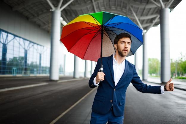 Porträt des jungen geschäftsmannes, der bunten regenschirm hält, der das auto am flughafen fängt