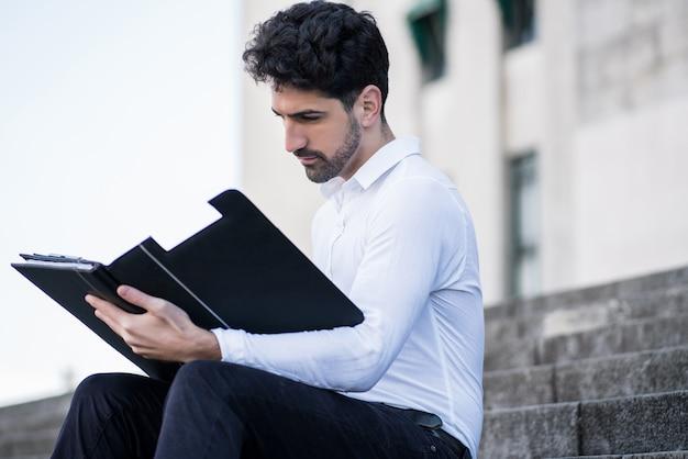 Porträt des jungen geschäftsmannes, der dateien liest, während er draußen auf treppen sitzt.