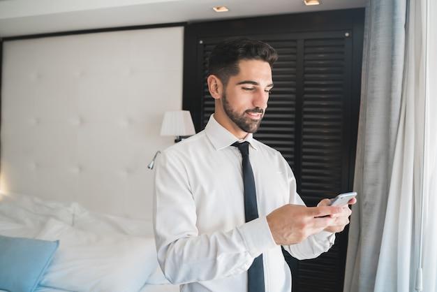 Porträt des jungen geschäftsmannes, der sein handy im hotelzimmer benutzt. geschäftsreisekonzept.
