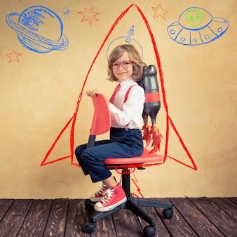 Porträt des jungen geschäftsmannes mit jetpack, der bürostuhl reitet