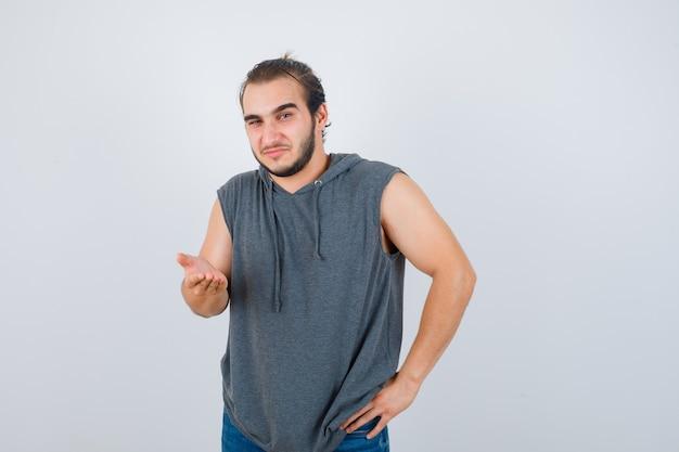 Porträt des jungen gesunden mannes, der handfläche an der kamera im ärmellosen kapuzenpulli ausbreitet und zögernde vorderansicht schaut