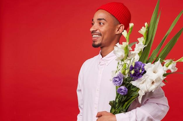 Porträt des jungen glücklichen afroamerikanischen attraktiven kerls, trägt im weißen hemd und im roten hut, schaut weg und hält blumenstrauß, steht über rotem hintergrund und lächelt.