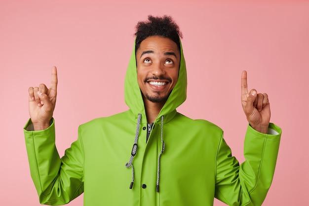 Porträt des jungen glücklichen afroamerikanischen gutaussehenden kerls steht, lächelt breit, will ihre aufmerksamkeit auf kopierraum lenken, finger zeigen und zu ihm aufblicken.