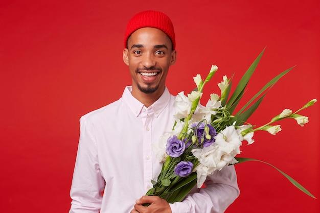 Porträt des jungen glücklichen afroamerikanischen mannes, trägt im weißen hemd und im roten hut, schaut in die kamera und hält blumenstrauß, steht über rotem hintergrund und lächelt.