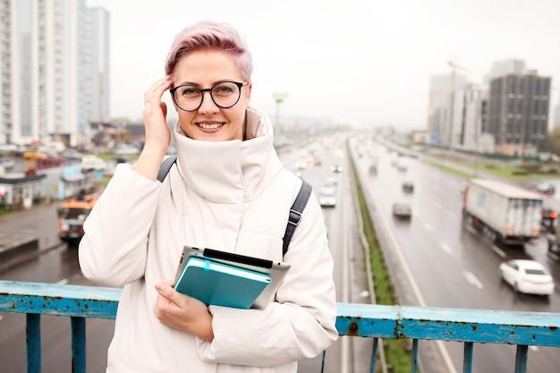 Porträt des jungen glücklichen bloggers mit modernem laptop und heften im freien