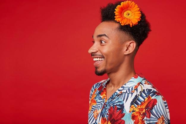 Porträt des jungen glücklichen dunkelhäutigen kerls, trägt im hawaiihemd, schaut mit glücklichem ausdruck weg, mit einer orange blume im haar, steht über rotem hintergrund.