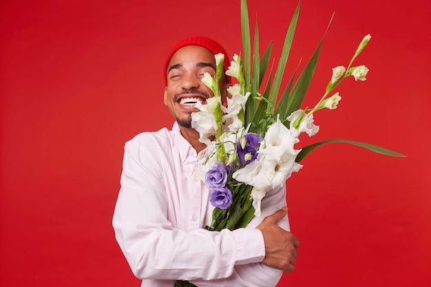 Porträt des jungen glücklichen dunkelhäutigen mannes, trägt im weißen hemd und im roten hut, mit geschlossenen augen umarmt blumenstrauß, steht über rotem hintergrund und lächelt.