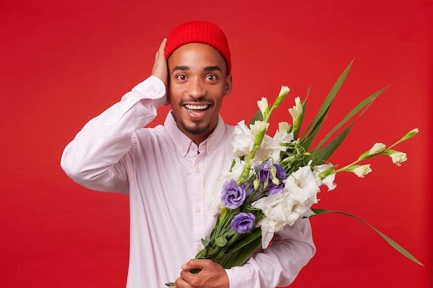 Porträt des jungen glücklichen erstaunten afroamerikaners, trägt im weißen hemd und im roten hut, schaut in die kamera und hält blumenstrauß, steht über rotem hintergrund und lächelt.