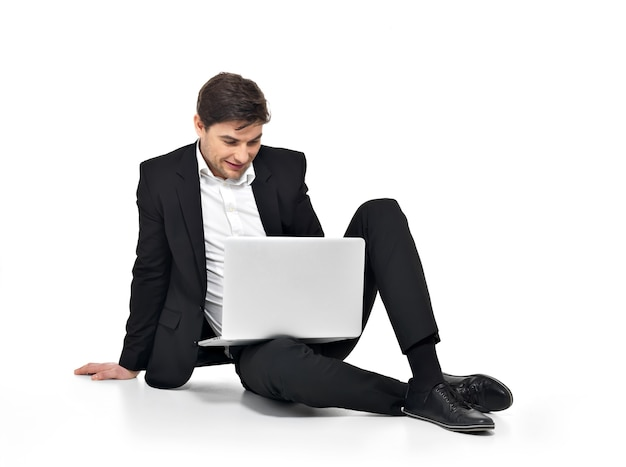 Porträt des jungen glücklichen geschäftsmannes, der auf laptop lokalisiert auf weiß arbeitet.