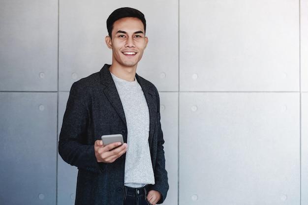 Porträt des jungen glücklichen geschäftsmannes using smartphone. stehen an der industriellen betonmauer