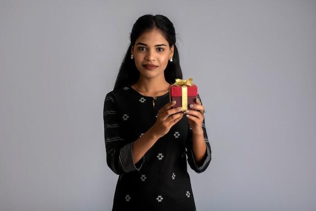 Porträt des jungen glücklichen lächelnden frauenmädchens, das geschenkbox auf einem grauen hintergrund hält.