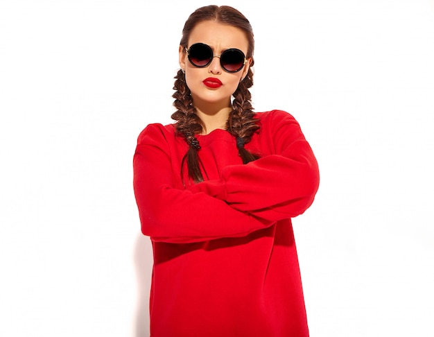 Porträt des jungen glücklichen lächelnden frauenmodells mit hellem make-up und den bunten lippen mit zwei zöpfen und sonnenbrille in der roten kleidung des sommers lokalisiert. verschränkte arme