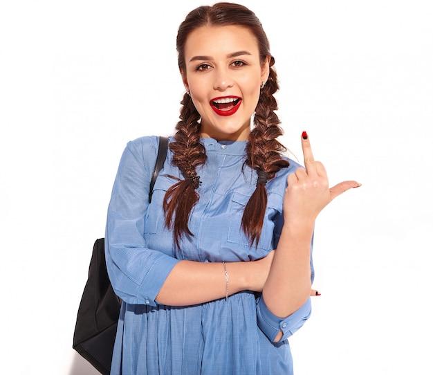 Porträt des jungen glücklichen lächelnden frauenmodells mit hellem make-up und den roten lippen mit zwei zöpfen in den händen im bunten blauen kleid und im rucksack des sommers lokalisiert. angezeigtes fuck off-zeichen